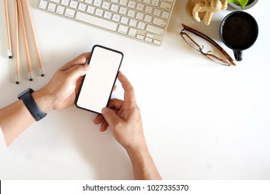 Man using mobile phone at office white desk table with desktop computer, office supplies and coffee mug. Top view workspace and blank screen smartphone