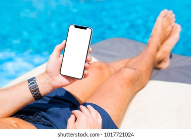 Man using mobile phone on vacation by the pool. Mobile phone mockup.