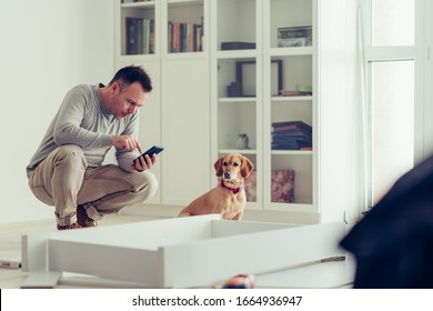 Man using a mobile phone while making furniture with his dog.