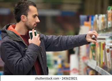 Man Using Mobile Phone While Shopping In Shopping Store