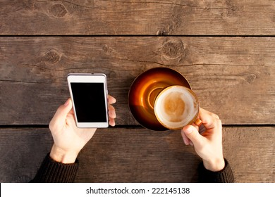 Man using mobile smart phone with coffee outdoors.