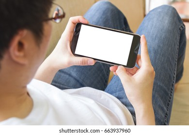 man using mobile smart phone with blank white screen in living room - clipping path inside