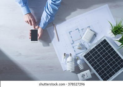 Man using a mobile touch screen smart phone next to a solar panel, a set of CFL lamps and a house project, energy saving concept