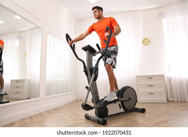 Man using modern elliptical machine at home