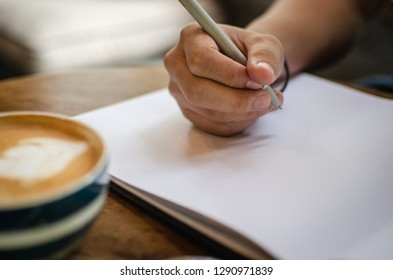 man using notebook in cafe