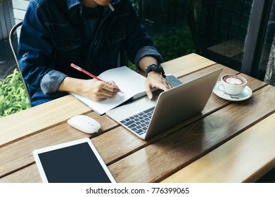 The man using pen to writing on notebook for business project with laptop, smart phone, touchpad, notbook