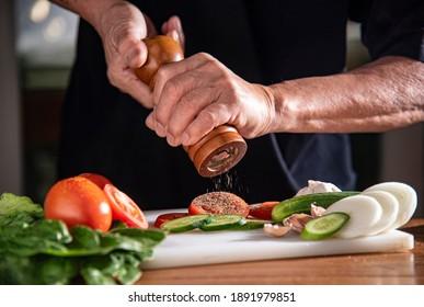 man using pepper grinder for cooking vegetable salad