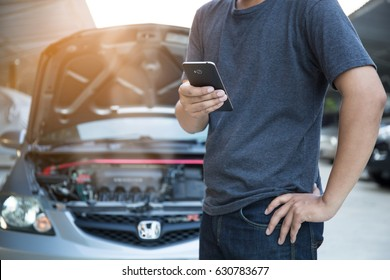 The man is using the phone in asking for help when his car is broken.