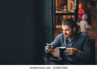 man using phone inside a restaurant while drinking cofee