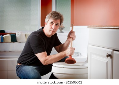 Man using a plunger to clear a plugged toilet