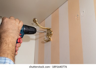 Man using a power screwdriver while installing a decorative wardrobe hook