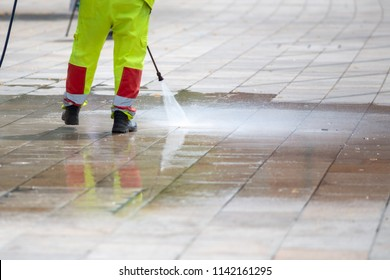 man using pressure washer to hose and clean the pavement and sidewalk