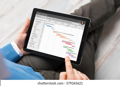 Man using project management app on tablet computer