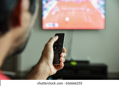 Man using remote control to switch channels. Close up hand holding apple tv remote