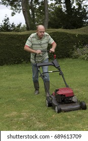 Man using a rotary lawn mower to cut his grass in rural England UK. July 2017