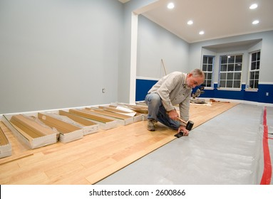 Man using a rubber mallet and tapping block to install the next row of laminate flooring. Do-it-yourself and renovation themes enhanced by uncovered wall outlets and power tools in the background.