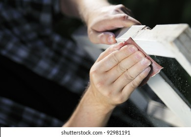 Man using sandpaper on an old window frame.