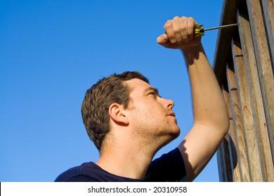 Man using screwdriver to fix porch. Horizontally framed photo.