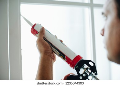 Man using a silicone gun to repair a window