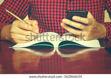 Man using smarphone make note about expenses at home.
