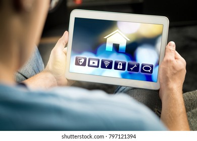 Man using smart home application in tablet to control house appliances. Internet of things (IOT) and remote controller app on smart device. Modern futuristic technology.