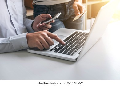 Man using smart phone and credit/debit card register payments online shopping and customer service network connection market, using technology on laptop, Internet Online shopping or banking concept.