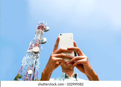 Man using smart phone devices with Telecommunication tower  blue sky background