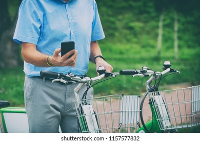 Man is using smart phone to rent bicycle from urban bicycle sharing station