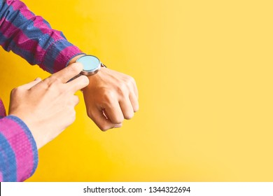 Man using smart watch for omnichannel. Smartwatch - modern digital gadget with empty display, copy space. Yellow background