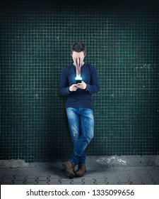 Man using smartphone against a wall. The concept of phone addiction. Face absorbed by the phone.