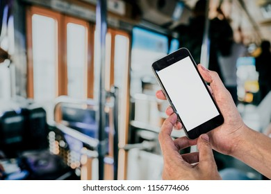 Man using smartphone with bus blurred background.Blank screen for graphics display montage.