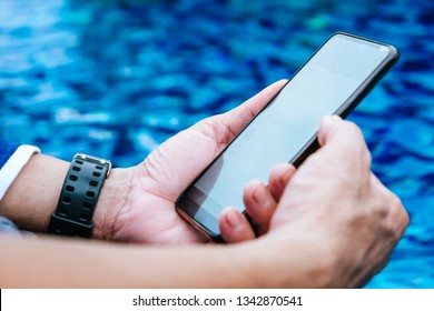 Man using smartphone by the pool