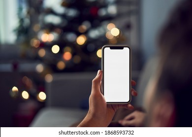 Man using smartphone during Christmas at home