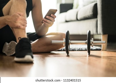 Man using smartphone during workout at home. Online personal trainer or on mobile phone. Internet fitness class or video course. Taking a break. Lazy guy with cellphone while training with dumbbell.