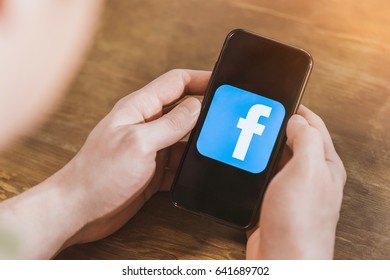 Man using smartphone with facebook logo icon on screen