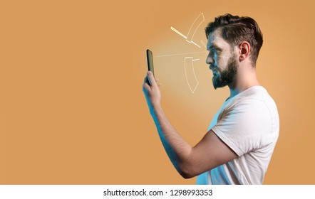 Man using smartphone and its facial recognition feature , copy space orange background