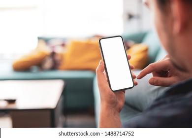 Man using smartphone frameless mockup blank screen in home interior