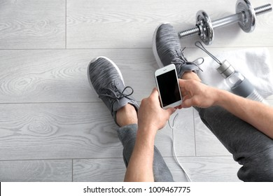 Man using smartphone in gym, top view