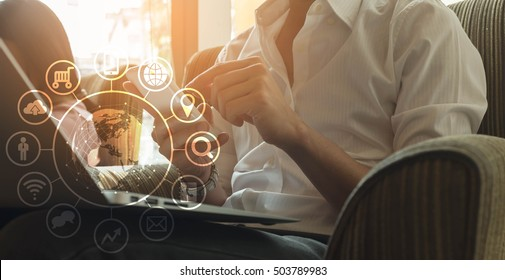 Man using smartphone and laptop in coffee shop, internet of things conceptual