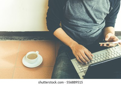 Man using smartphone and laptop.filter color effect.