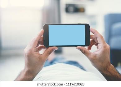 Man Using Smartphone Lying on a Floor at Home. First person view.  Clipping path included.