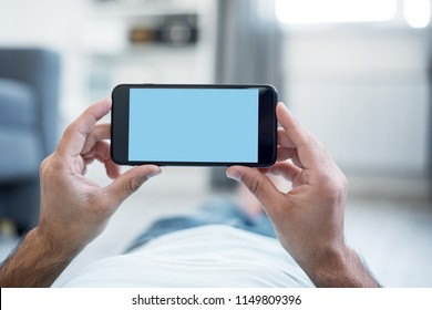 Man Using Smartphone Lying on a Floor at Home. View from above. Clipping path included.