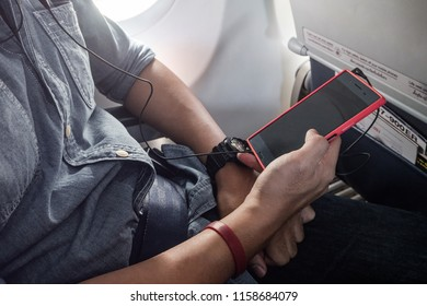 A man using smartphone on airplane, Young passenger man listening music on airplane, Smart technology, on airplane, Relax time with good music