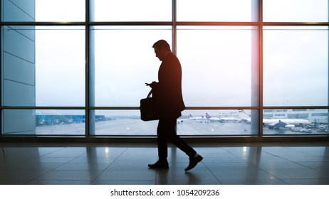 A man using smartphone on a business trip at the airport. Sun flare effect