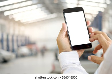 Man using smartphone over blurred garage background.
