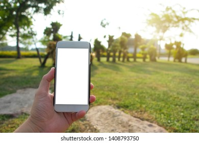 man using smartphone at park, GPS navigation , white screen frame on smartphone in hand with blur image of tree in park or garden