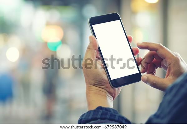 Mann, der bei Straßennacht Smartphone benutzt. Blank Bildschirm Handy für grafische Display-Montage.