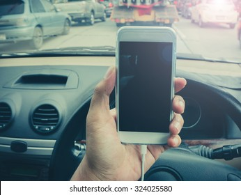 man using a smartphone while driving a car with a filter effect