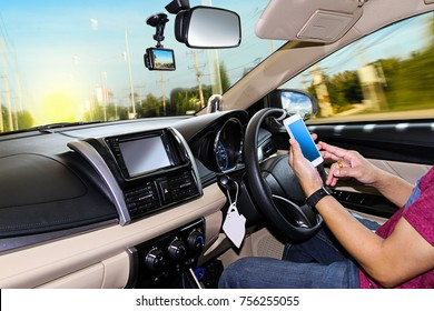 A man using a smart-phone while driving a car on the road.