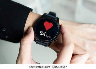 Man using a smartwatch with app checking heart rate.
